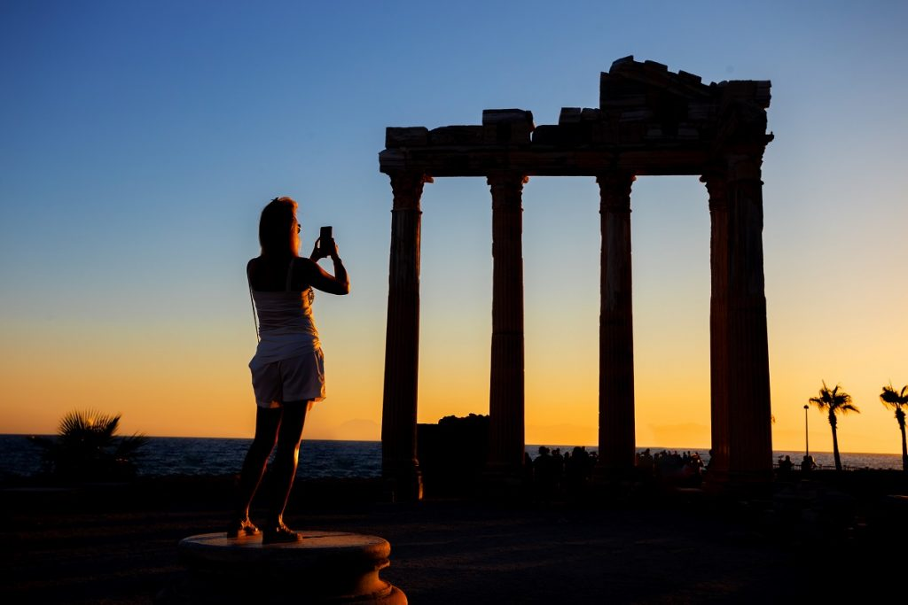 Silhouette of girl photographing on phone Temple of Apollo at sunset