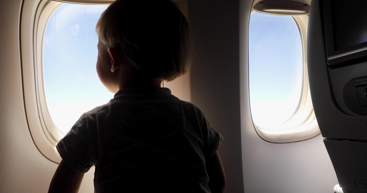 Child is watching from the window of the porthole for the flight of the aircraft
