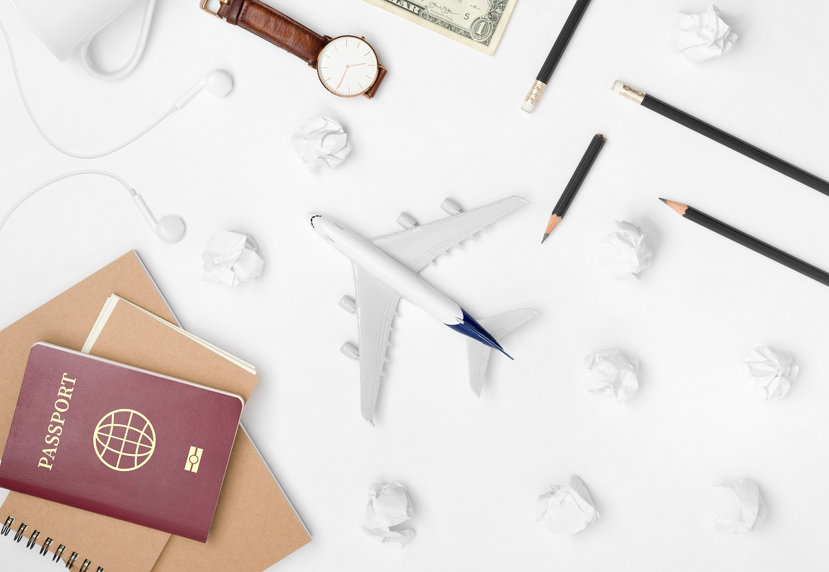 Travel Planning. Airplane, pencil, watch, money, paper note, notebook, earphone, and passport with blank space on white background. Preparation for Traveling and Flat lay Concept.